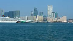 Small container ship transiting the bay beneath the highrise buildings Stock Footage