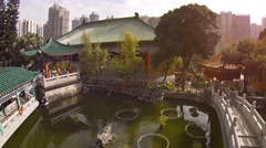 Bridge over pond in garden courtyard of Wong Tai Sin Buddhist temple Stock Footage