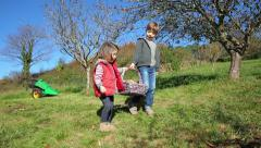 Happy children carrying wicker basket with apples harvest Stock Footage