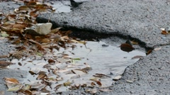 Bad asphalt tarmac rain pits in a pool of floating leaves are falling drops of Stock Footage