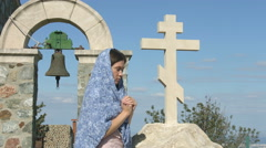 Religious woman praying to God, crossing herself, looking into the sky with hope Stock Footage
