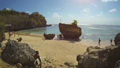 Tourists wading behind enormous rock formations on a popular tropical beach - stock footage