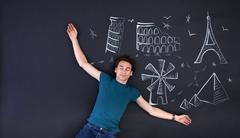 Young man playing with a draw that shows the world attractions. Stock Photos