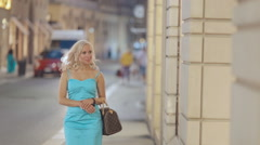 Stylish girl looking in the shopwindow of luxury clothing stores Stock Footage