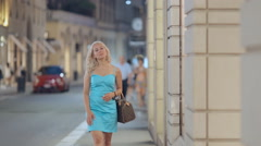 Shopaholic woman looking in the windows of boutiques while walking in Milan - stock footage