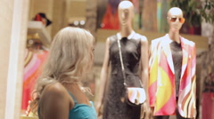 Woman looks admiringly at the windows of boutiques in Milan - stock footage