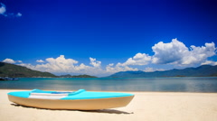 Blue white metal paddle boat on gold sand by azure sea beach Stock Footage