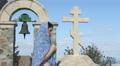 Young female parishioner saying prayers outside church, touching stone cross Footage