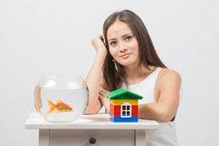 A young girl sits next to a round aquarium in which swimming goldfish - stock photo