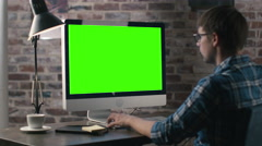 Young man is working on a computer with a mock-up green screen - stock footage