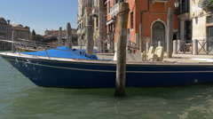 Blue boat moored to a wooden mooring post in Venice Stock Footage