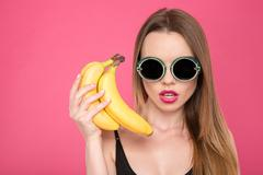 Closeup of young female in glasses holding bananas - stock photo