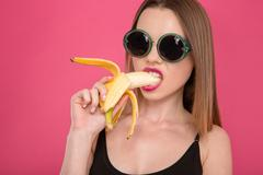 Closeup of young seductive model eating banana Stock Photos
