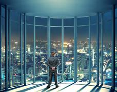 Night view of buildings and man from glass window Stock Photos