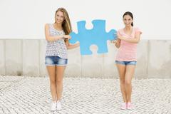 Students holding a puzzle piece - stock photo