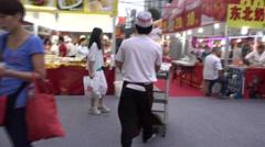 Follow a waiter walk into food festival in guangzhou Stock Footage