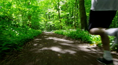 Sporty Young Man Running On Trail In Forest Stock Footage