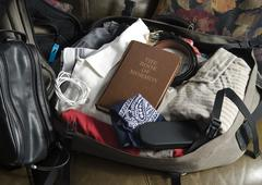 The Book of Mormon in packed mans suitcase Stock Photos