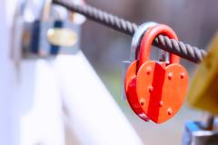 Heart shape padlock on bridge railing - stock photo