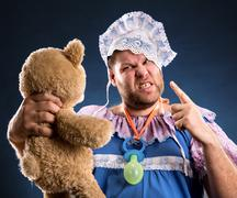 Angry man with toy bear - stock photo