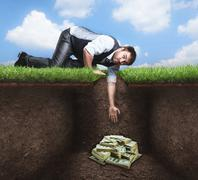 Businessman trying to get treasure in the soil - stock photo
