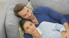 Upper view of young couple laying in sofa Stock Footage