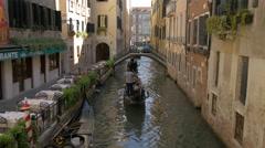 Paddling gondolas under a small bridge in Venice Stock Footage