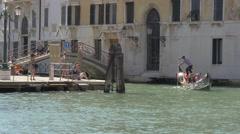 Man paddling a boat near a small bridge in Venice Stock Footage