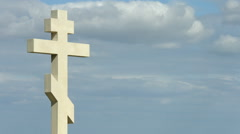 Time-lapse of gray clouds flying over stone cross on grave at the cemetery - stock footage