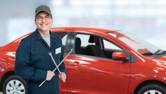 Auto mechanic with tire wrench in garage. - stock photo