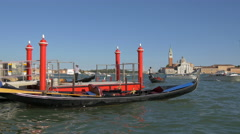 Gondolas moored to a pier with four red posts in Venice Stock Footage