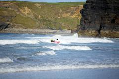Kayaker riding waves at ballybunion Stock Photos