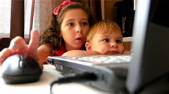 Children (girl and boy) looking at laptop at home Stock Footage