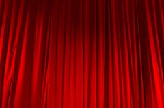 Red closed curtain with light spots in a theater Stock Photos