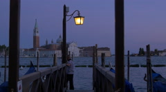 Gondolier standing on the waterfront in the Venetian Lagoon, Venice Stock Footage