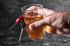 man behind car key and glass of liqueur - stock photo
