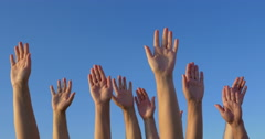 Raised hands against blue sky Stock Footage