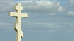 Time-lapse of gray clouds flying over stone cross on grave at the cemetery Stock Footage