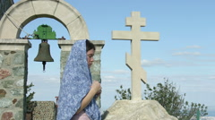 Young female parishioner saying prayers outside church, touching stone cross Stock Footage