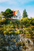 Wooden house cottage on top of cliff or rock, summer evening Stock Photos