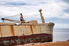 Abandoned wreck old ship near shore - stock photo
