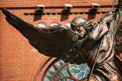Statue Of Archangel Michael near Red Catholic Church Of St. Simo - stock photo