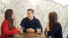 Boy and two girls laughing and talk in cafe Stock Footage