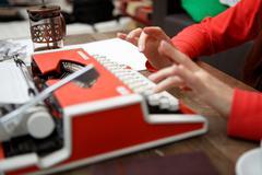 woman at table typing on typewriter - stock photo