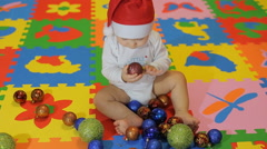 Happy Baby with Santa cap playing with Christmas red decorations Arkistovideo