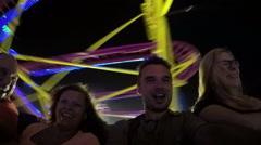 People enjoying roller coaster ride at night Stock Footage