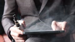 Businessman with an e-cigarette and reads his tablet computer Stock Footage