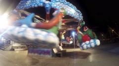 Children enjoy entertainment ride at night in luna park - stock footage