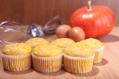 Six cupcakes, pumpkin and baking kitchenware on wood texture table Stock Photos