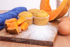 Three cupcakes, pumpkin and baking kitchenware on kitchen Stock Photos